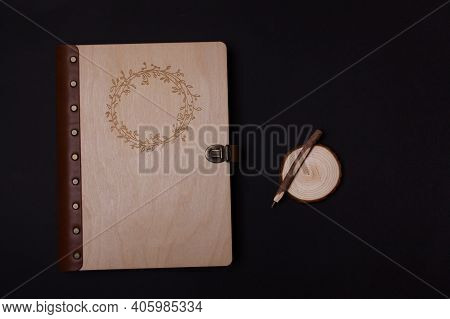 Family Photo Book With Embossing. Photo Book On A Dark Background. Brown Photo Book With Wood Cover.