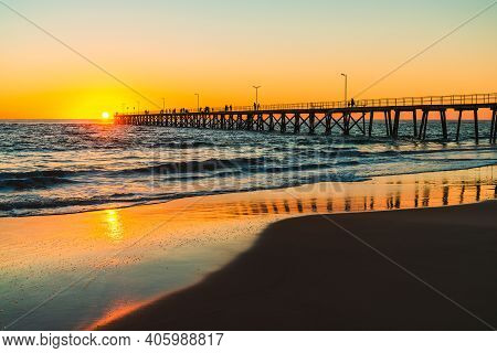 People Silhouettes On Port Noarlunga Jetty Biewed From The Beach At Sunset, South Australia