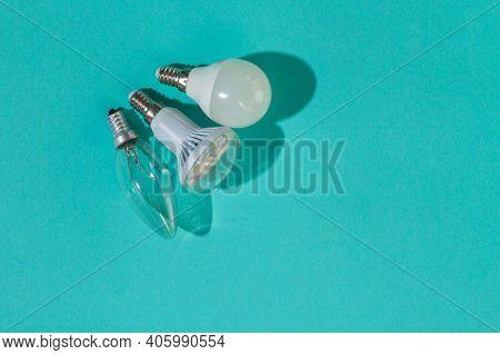 Three Light Bulbs On A Blue Background: Incandescent Light Bulb, Led Light Bulb, Fluorescent Light B