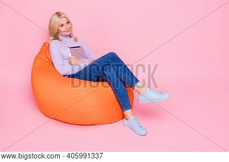 Full Length Body Size Photo Of Old Lady Thoughtful Dreamy Keeping Tablet In Orange Beanbag Isolated