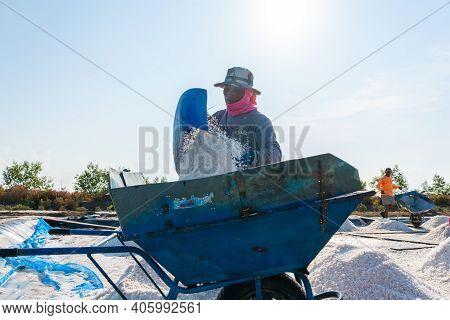 Samutsongkram, Thailand - March 10, 2019: Salt Farmer Is Gathering Salt Into Wheelbarrow On Salt Far