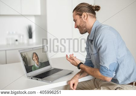 Young Handsome Hipster Guy Sitting At The Desk At The Home Office And Talking To Virtual Old Lady Fr