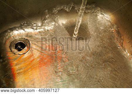 Water Splashing Down The Sink On Stainless Kitchen Sink. Scene Water Splashing Pouring Strong Of Wat