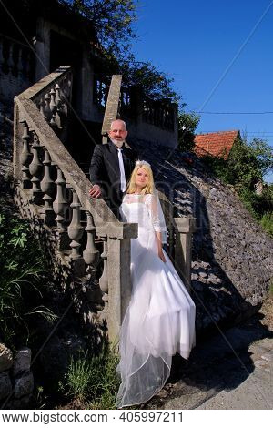 Wedding Concept. The Happy Handsome Wedding Couple Are Standing Steps In Front Of House. Romantic Gr