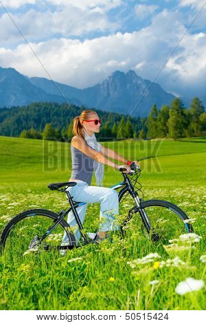 Active woman on bicycle in mountains, beautiful landscape, active lifestyle, riding on pushbike, sportive life, summer holidays in Europe