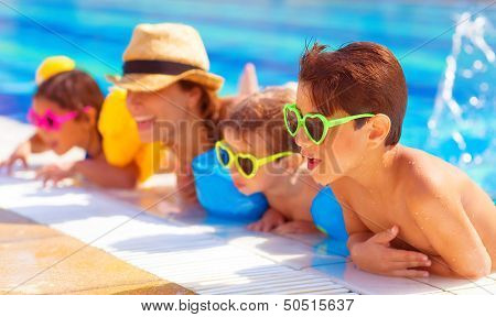 Happy family in the pool, having fun in the water, mother with three kids enjoying aquapark, beach resort, summer holidays, pleasure concept  poster