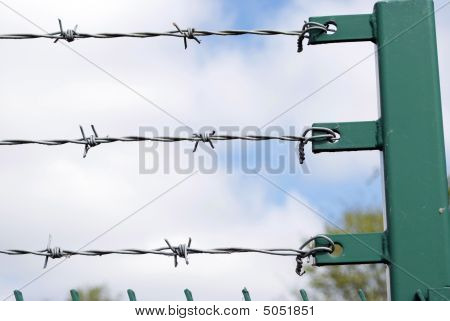 Royalty Free Stock Image of three rows of barbed wire against cloudy blue sky with post to right copyspace provided poster