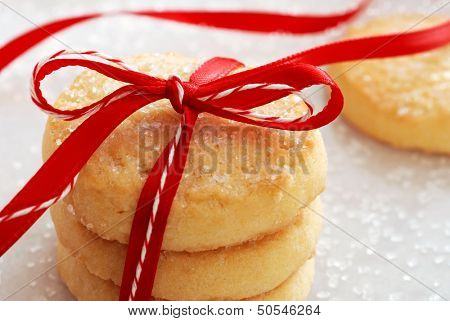 Freshly baked sugar cookies tied with festive bakers twine and red satin ribbon.  Decorating sugar crystals sprinkled in background.  Macro with shallow dof.