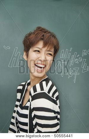 Portrait of bilingual woman in front of blackboard