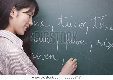 Young woman student writing English numbers on blackboard