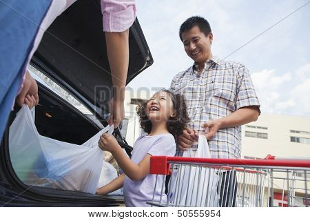 Family talking next to the car with shopping bags