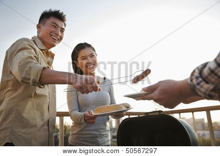 Son giving sausage to his father over the barbeque
