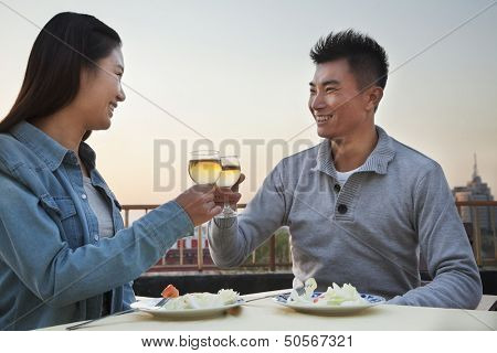 Young couple eating on the roof top, toast