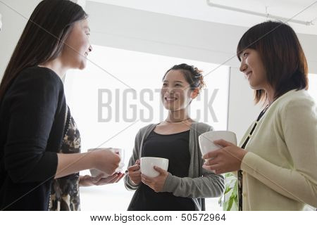 Three businesswomen on the coffee break in the office