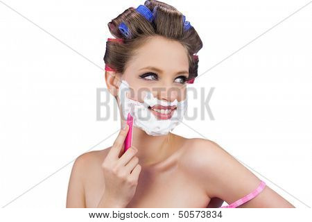 Cheerful lady in hair curlers posing with razor on white background