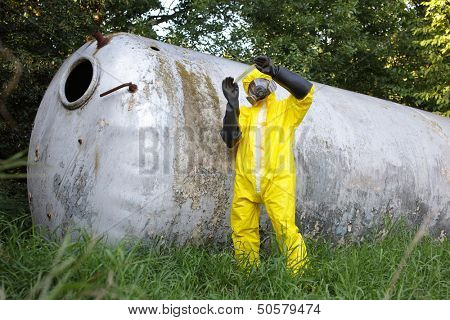 technician in protective uniform,mask, and gloves examining sample from large stainless tank