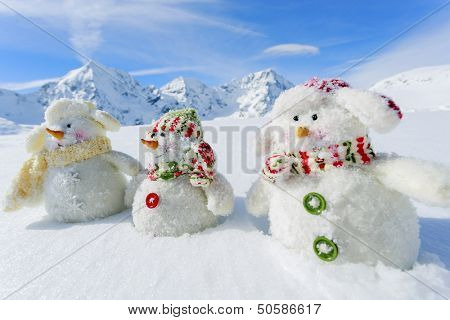 Winter, snow, sun and fun,  Christmas - happy snowman friends and snowy mountains in background