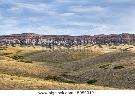 rolling prairie and cliff illuminated by sunrise at Soapstone Prairie Natural Area in northern Colorado near Fort Collins, late summer