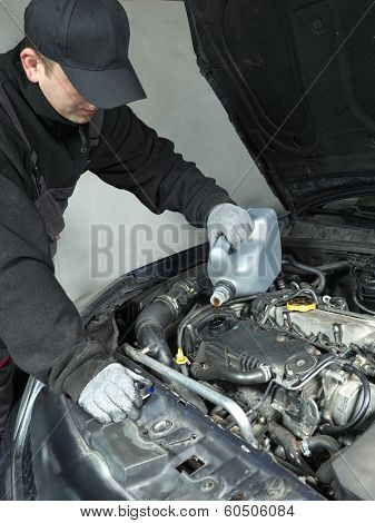 Auto mechanic replenishing engine oil