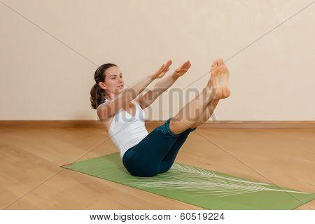 Caucasian woman is practicing yoga at studio (paripurna navasana) poster