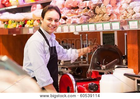 Shopkeeper cutting ham in a grocery store poster