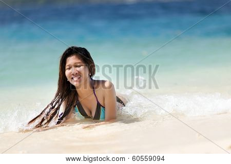 Attractive young Filipina woman swimming in the sea laughing as she lies in the shallow surf enjoying the summer sunshine