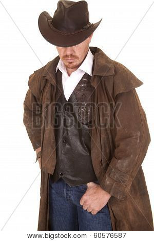 A cowboy in a vest and leather duster and hat looking down. poster