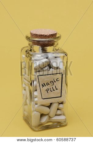 Closeup of an old fashioned pill bottle filled with Magic Pills. The Clear Glass bottle has a label with the words Magic Pill. Vertical format on a pale yellow background.