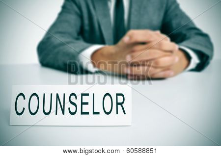 a man wearing a suit sitting in a desk with a desktop nameplate in front of him with the word counselor poster