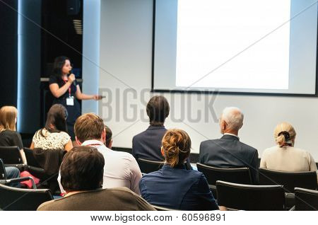 Business Conference. People Sitting Rear And Woman Speaking At The Screen