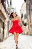 Happy beautiful woman in red summer dress walking and running joyful and cheerful smiling in Venice, Italy. Pretty sexy fashion model girl in her 20s. Mixed race Asian Caucasian female model outside. poster