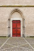Wooden entrance door with decorative fittings in arch shaped wall recess of the Saint Walburga Church in the Hanse town Zutphen the Netherlands poster