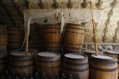Stacked oak wine barrels in winery cellar poster