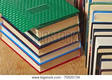 Stack And A Number Of Books On A Wooden Surface.