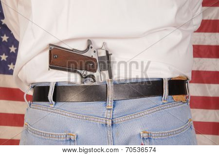 Man with a semi-automatic pistol stuck in his waistband in front of an American flag