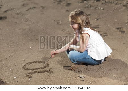 Girl Writing Number In The Sand
