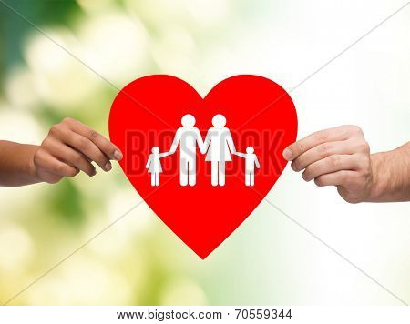 health, love, adoption and relationships concept - closeup of multiracial couple hands with big red heart with family and kids over green background