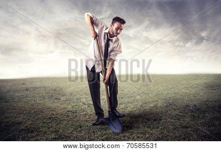 businessman digging in a field
