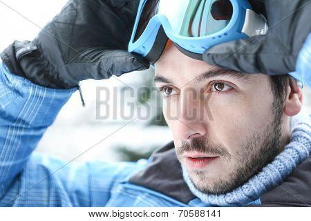 Man in ski holiday putting on his ski googles in winter