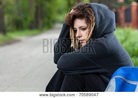 Depressed Girl In Hood Sitting Down On Road