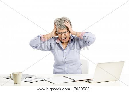 Stressed elderly woman working in the office with a laptop