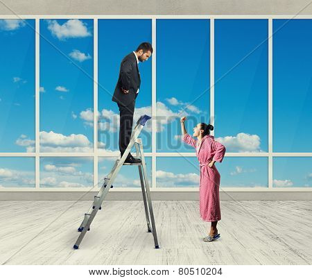 emotional woman screaming at her husband on the stepladder in office with big windows poster