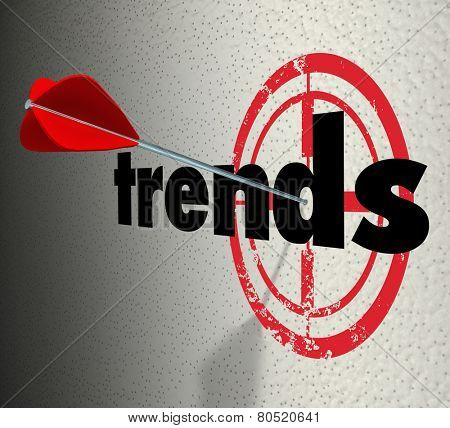 Trends word on a wall with bulls-eye and arrow hitting the target to illustrate fads or current popular products