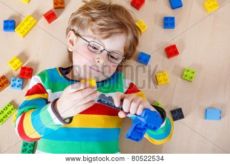 Little blond kid boy playing with lots of colorful plastic blocks indoor. child wearing colorful shirt and glasses having fun with building and creating. poster