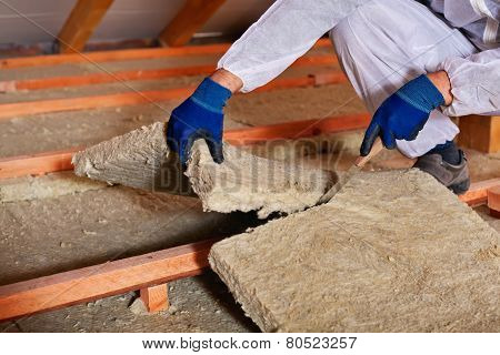 Installing thermal insulation layer - closeup on hands cutting rock wool poster