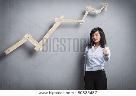 Concept: Successful career or business. Young confident businesswoman holding thumb up in front of ascending business graph, isolated on grey background.