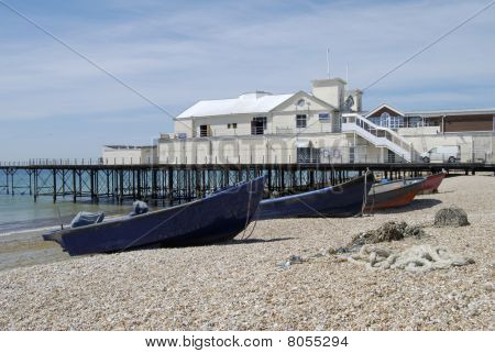 Fishing boats and lobster pots on shingle beach by the pier at Bognor Regis. West Sussex. England poster