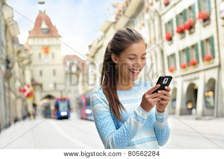 Woman on smart phone walking on Kramgasse, Berne main street in the old city. Young female using smartphone app visiting tourist attractions and landmarks. poster