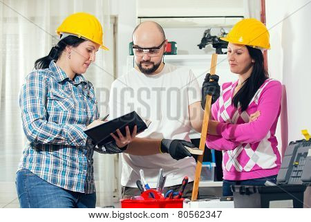 Craftsman and two craftswoman in workshop, selective focus