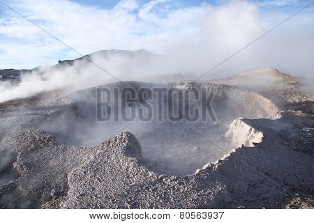 Geyser with mud and vapor above in Bolivia